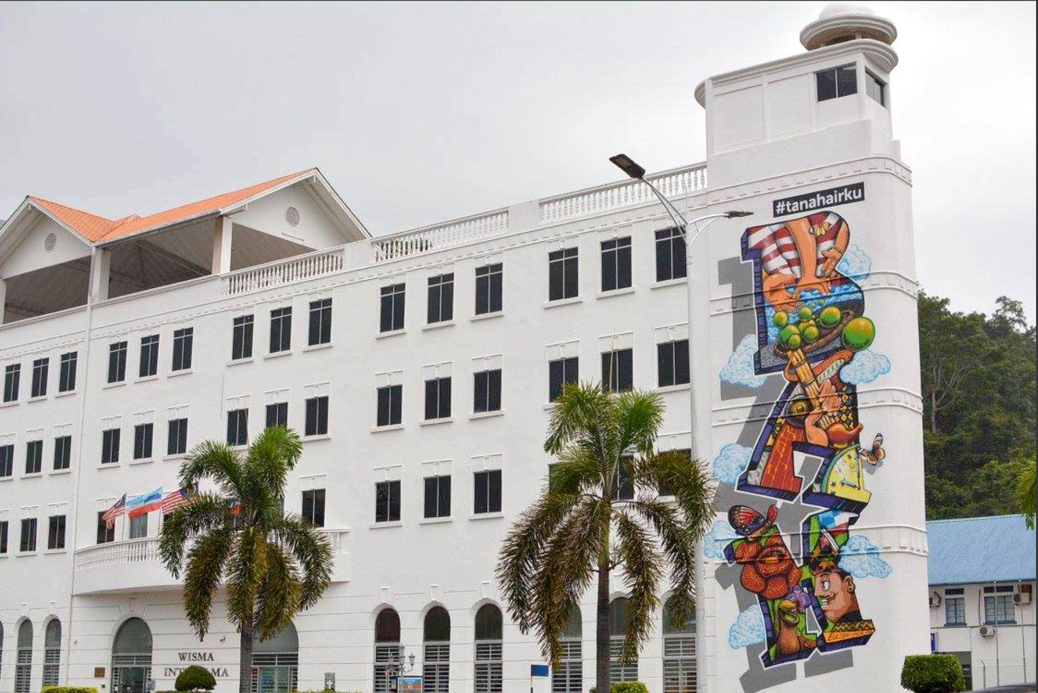 Foundation of Local Patriotism: A Kota Kinabalu street art of Cracko Art Group welcomed Juria Garcia in October 2015. It is a depiction of the Kadazan god's daughter, Huminodun, the inspiration for the Harvest Festival beauty queen on the three-storey wall of Wisma Sabah. Inspired by the colours of the Malaysian and Sabah flag, the mural instils a sense of patriotic pride and unity. This mural was painted by Harold Reagan Eswar, Kwan Thung Seng and Anddy Romeo Dulait. Another Petronas commissioned CAG mural can be seen at the facade of the Wisma Intiutama at Lorong Dewan. Set against the background of wind and clouds to strongly denote its place of origin, BAH is a colloquial word for Sabahans to express various kinds of emotions, making it a richer language.